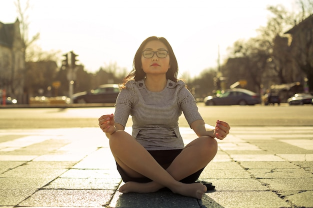 Mujer asiática meditando en la calle