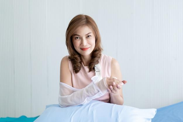 Mujer asiática mirando su brazo herido por accidente. concepto de salud y bienestar en personas adultas.