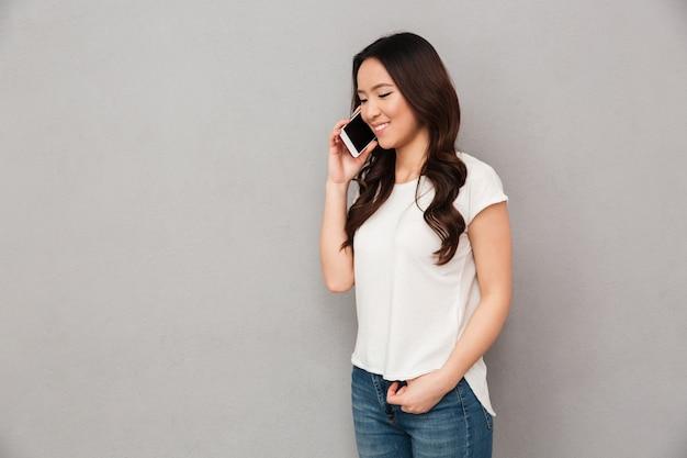 Mujer asiática moderna en camiseta casual y jeans con llamada móvil con smartphone, aislado sobre pared gris