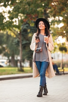 Mujer asiática moderna que sostiene el teléfono móvil y la taza de café mientras camina en el parque al aire libre
