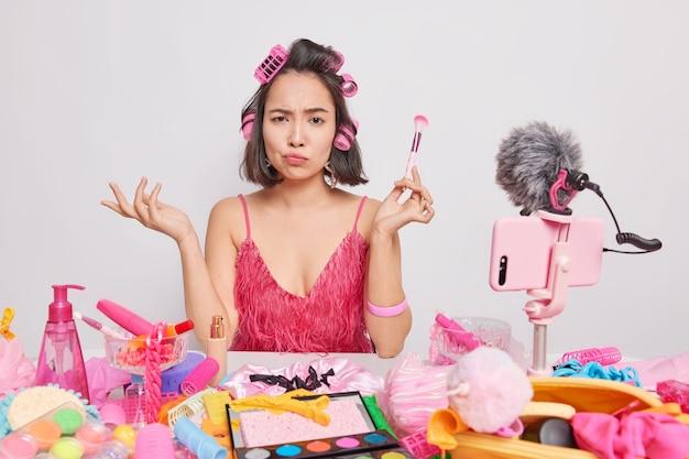 La mujer asiática morena descontento mira con expresión indignada sostiene cepillo cosmético