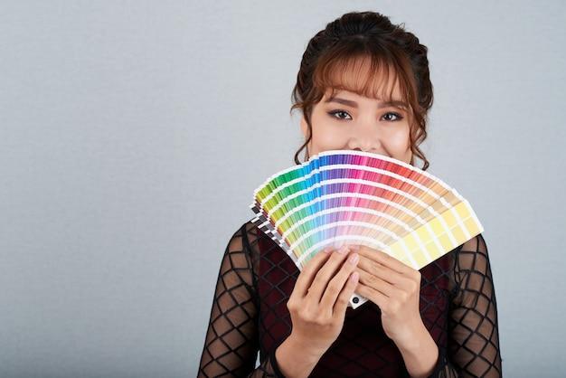Mujer asiática mostrando paleta de colores cubriendo su boca con ella