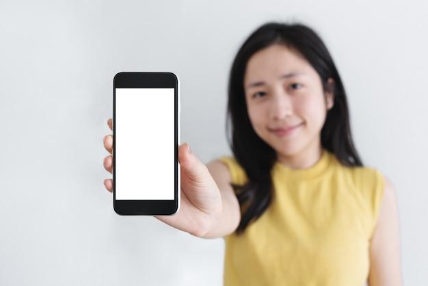 Mujer asiática mostrando teléfono inteligente móvil con cara sonriente, pantalla blanca vacía