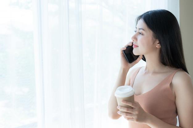 Mujer asiática de la muchacha linda hermosa que juega un teléfono elegante en el dormitorio blanco de la mañana