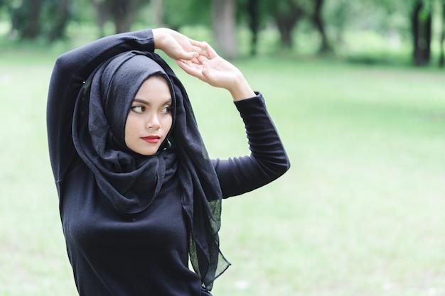 La mujer asiática musulmán joven hermosa que hace ejercicio antes de correr encima empañó el campo verde