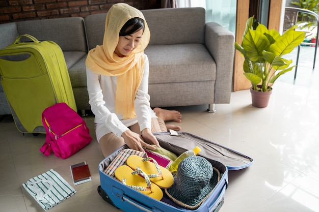 Mujer asiática musulmana preparando y empacando