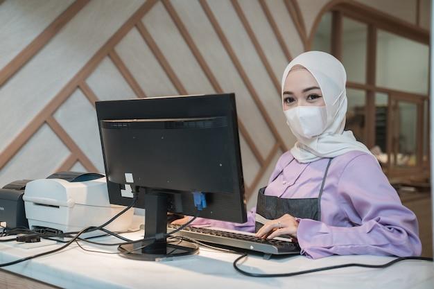 Mujer asiática musulmana que trabaja con pc mientras usa mascarilla médica para protección en la oficina