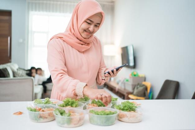 Mujer asiática musulmana servicio de catering a domicilio preparando lonchera para comida para llevar pedido en línea