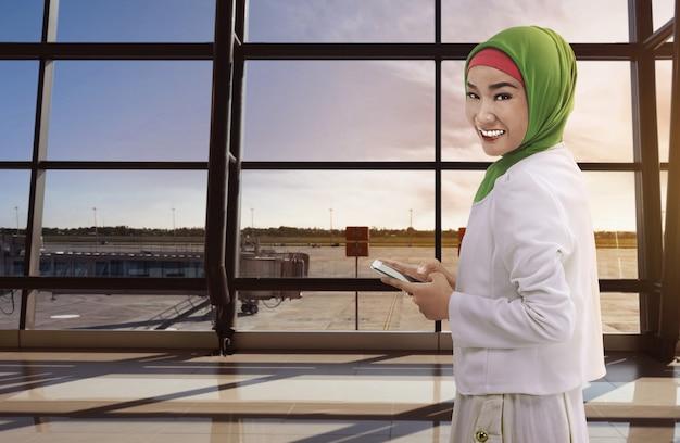Mujer asiática musulmana sosteniendo el teléfono