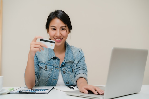 Mujer asiática del negocio elegante hermoso que usa el ordenador o el ordenador portátil que compra compras en línea por la tarjeta de crédito mientras que lleva la sentada casual elegante en el escritorio en sala de estar en casa.