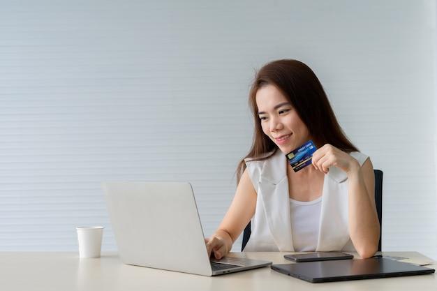 Mujer asiática de negocios joven con tarjeta de crédito y usando laptop