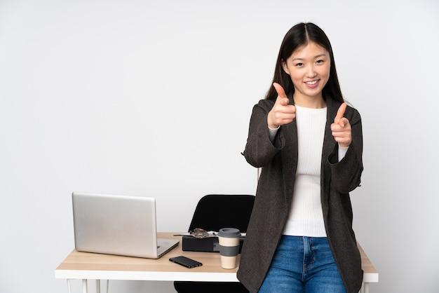 Mujer asiática de negocios en su lugar de trabajo en la pared blanca apuntando hacia el frente y sonriendo