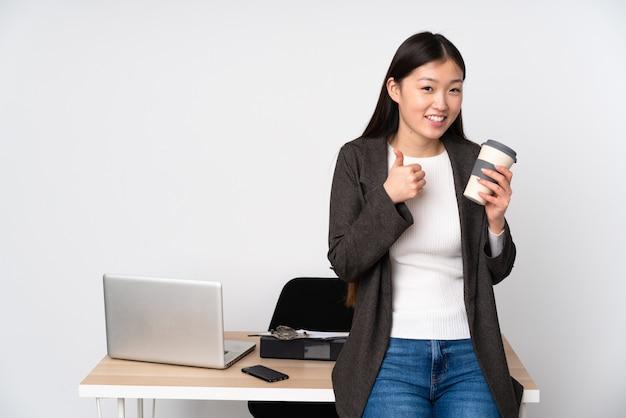 Mujer asiática de negocios en su lugar de trabajo en la pared blanca dando un gesto de pulgares arriba
