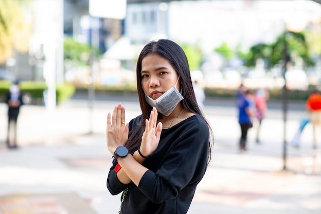 La mujer asiática no usa una mascarilla para protección contra virus o contaminación signo de mano incorrecto sobre fondo de prople al aire libre. nuevo concepto normal. firmar.