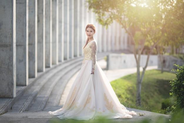 Mujer asiática novia en vestido de novia en pradera
