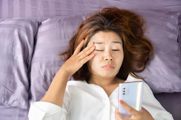 Mujer asiática ojos cansados de ver la pantalla del teléfono en la cama