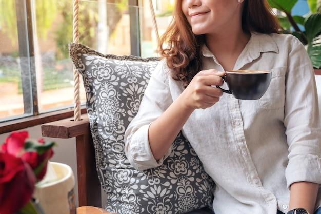 Mujer asiática oliendo y bebiendo café caliente con sentirse bien en la cafetería