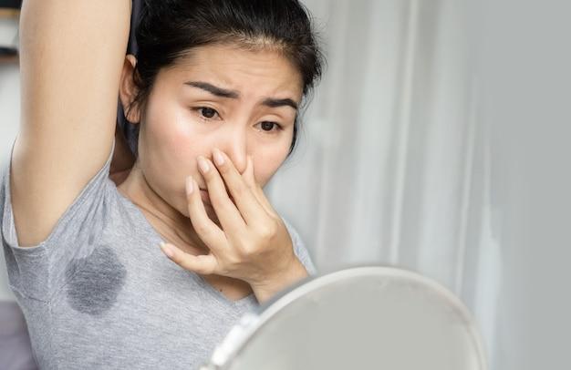 Mujer asiática oliendo su axila maloliente y sudorosa