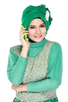 Mujer asiática con pañuelo en la cabeza llamando por teléfono móvil