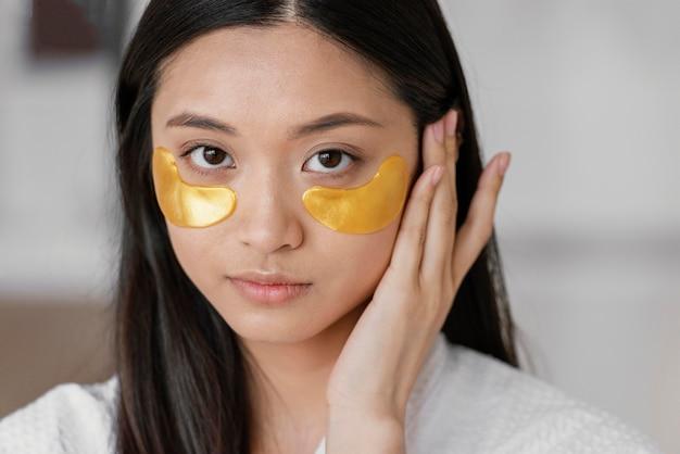 Mujer asiática con parches en los ojos