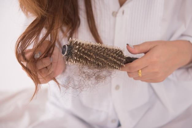 Mujer asiática pelo largo con un peine sobre fondo blanco.