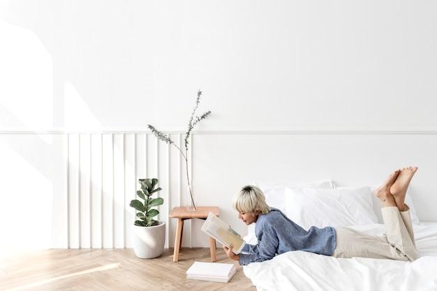 Mujer asiática de pelo rubio leyendo un libro sobre un colchón en el suelo