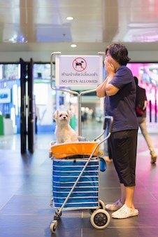 Mujer asiática y el perro con signo. no se admiten mascotas.