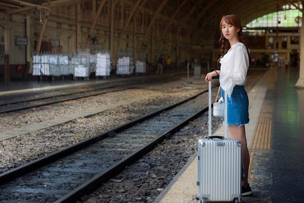 Mujer asiática está de pie en la plataforma y esperando el tren en la estación de tren