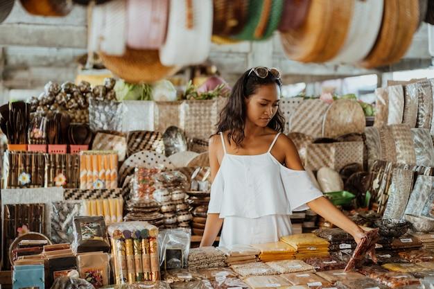 Mujer asiática con piel bronceada en la tienda de souvenirs