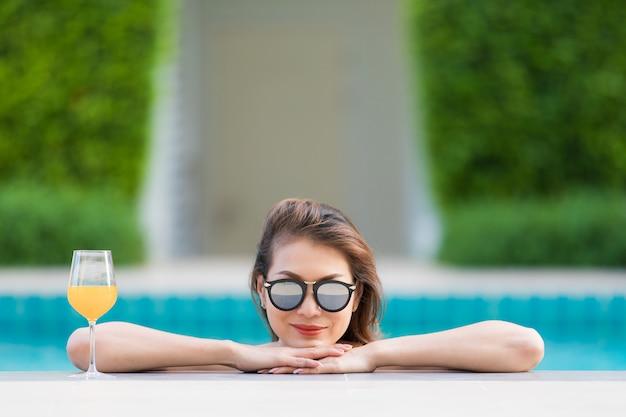 Mujer asiática en piscina con vaso de jugo de naranja