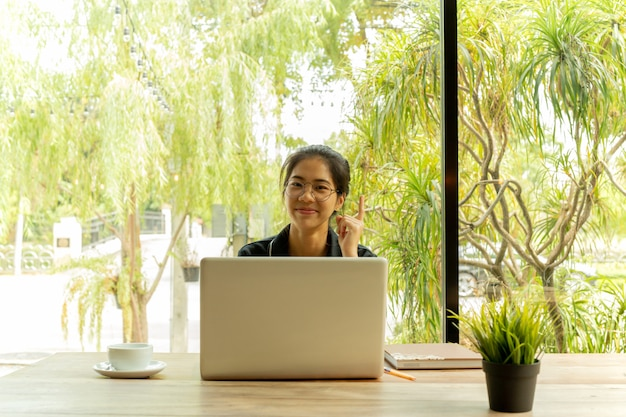 La mujer asiática pone el finger para arriba que piensa en idea con el ordenador portátil en cafetería.