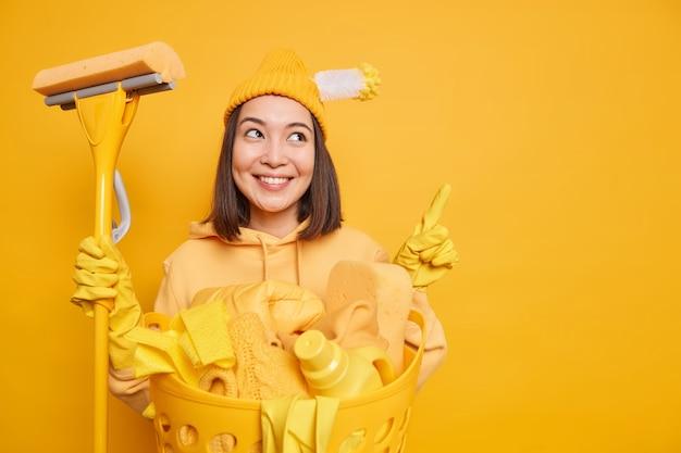 La mujer asiática positiva ocupada lavando ropa viste poses de ropa casual con artículos de limpieza puntos arriba en el espacio de la copia da consejos sobre cómo limpiar todo muy rápidamente aislado sobre una pared amarilla