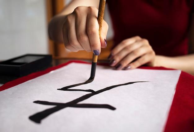 Mujer asiática practicando escritura japonesa en interiores