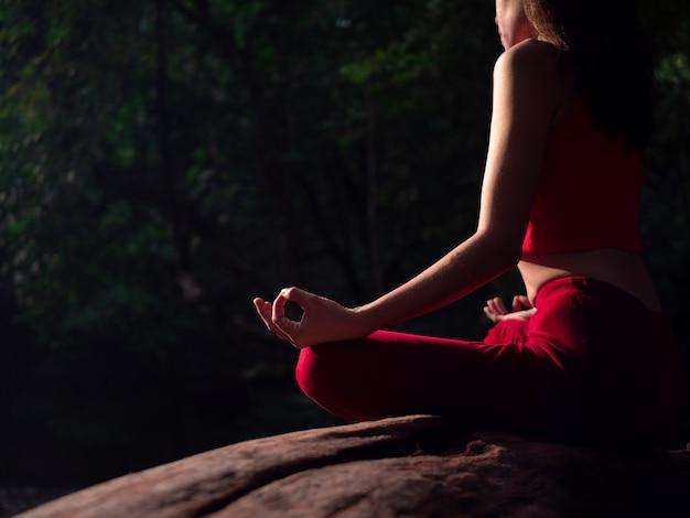 Mujer asiática practicando o haciendo yoga en la cascada