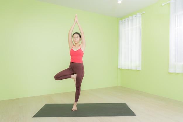 Mujer asiática practicando yoga en una estera negra, de pie en pose de árbol.