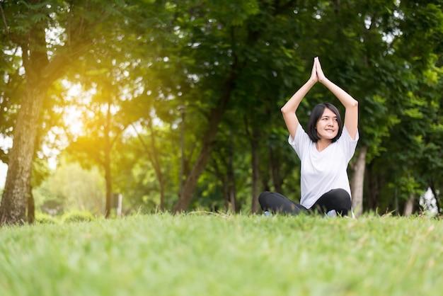 Mujer asiática practicando yoga en el parque por la mañana, feliz y sonriente, pensamiento positivo, concepto de estilo de vida saludable y