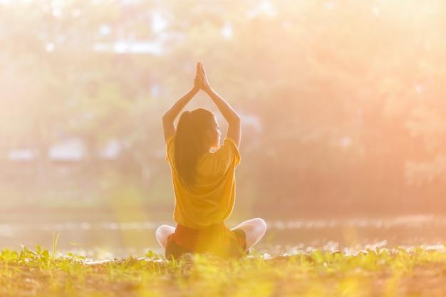 Mujer asiática practicando yoga pose de guerrero