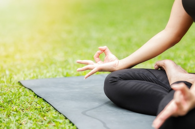 Mujer asiática practicando yoga en root bond, mula bandha plantean sobre la colchoneta en el parque al aire libre.