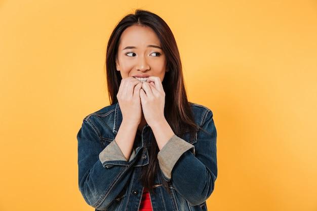 Mujer asiática preocupada en chaqueta muerde los dedos y mirando a otro lado