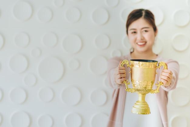 Mujer asiática presente trofeo de oro.