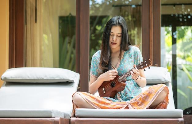 Mujer asiática del primer que toca el ukelele en el sofá en la terraza