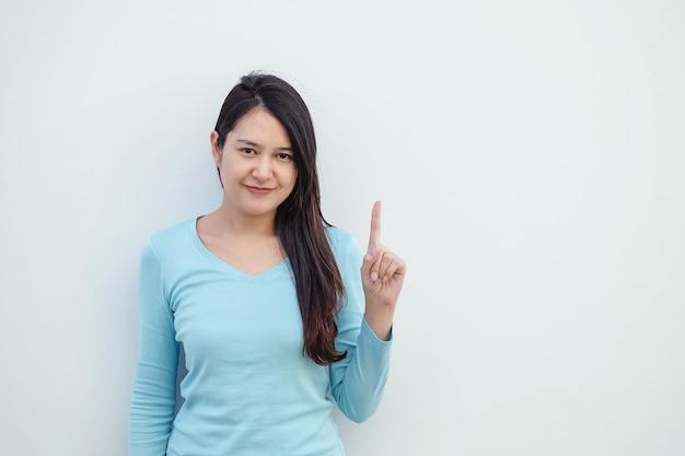 La mujer asiática del primer soporta un movimiento del dedo con la cara de la sonrisa en el fondo blanco de la pared del cemento con el espacio de la copia