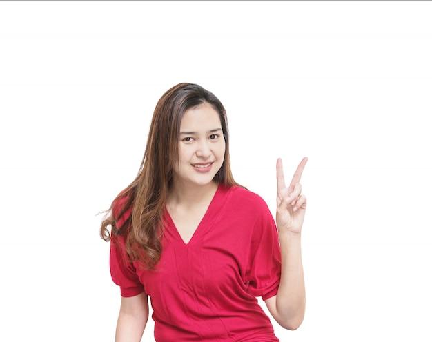 La mujer asiática del primer soporta el movimiento de dos dedos con la cara de la sonrisa aislada