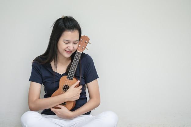 Mujer asiática del primer con el ukelele en el fondo de la textura de la pared del cemento blanco