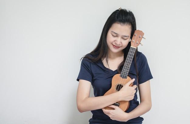 Mujer asiática del primer con el ukelele en la textura de la pared del cemento blanco