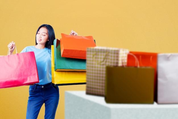 Mujer asiática, proceso de llevar, bolsas de compras, posición