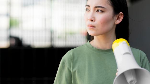Mujer asiática protestando y sosteniendo megáfono