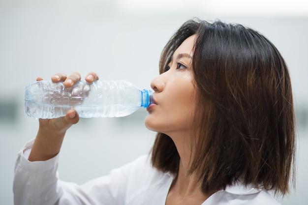 Mujer asiática que bebe agua de la botella plástica