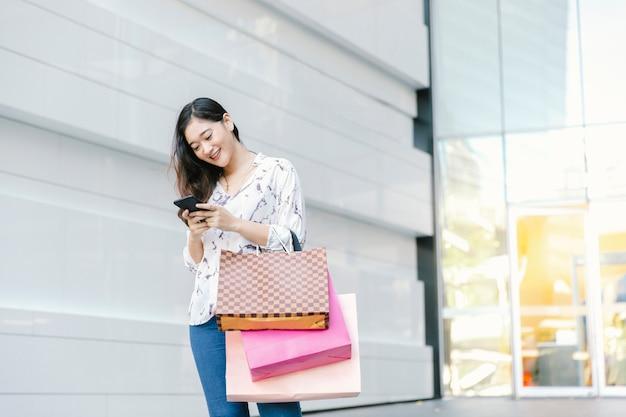 La mujer asiática que comprueba el teléfono inteligente y la sonrisa con los bolsos de compras goza en centro comercial
