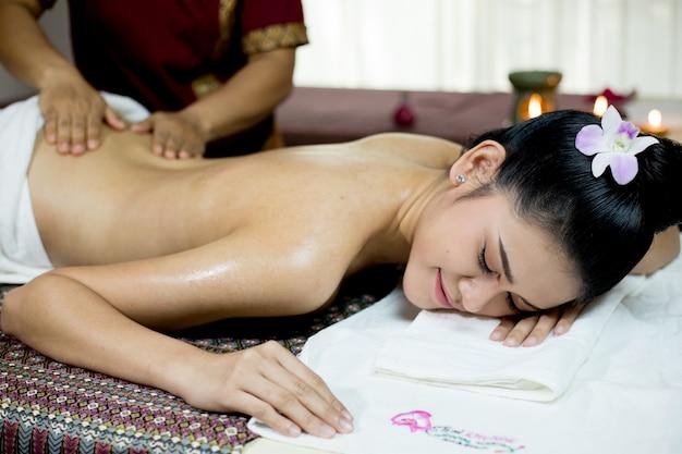 Mujer asiática que consigue masaje tailandés de la compresa herbaria en balneario